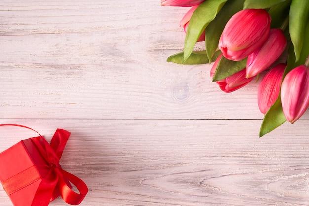Różowe tulipany i pudełko z czerwoną wstążką