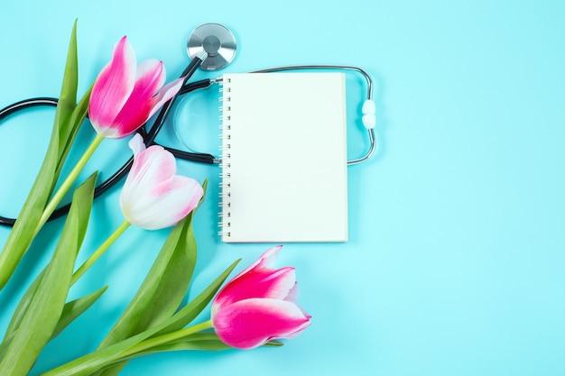 Różowe tulipany i stetoskop ze spiralnym notatnikiem