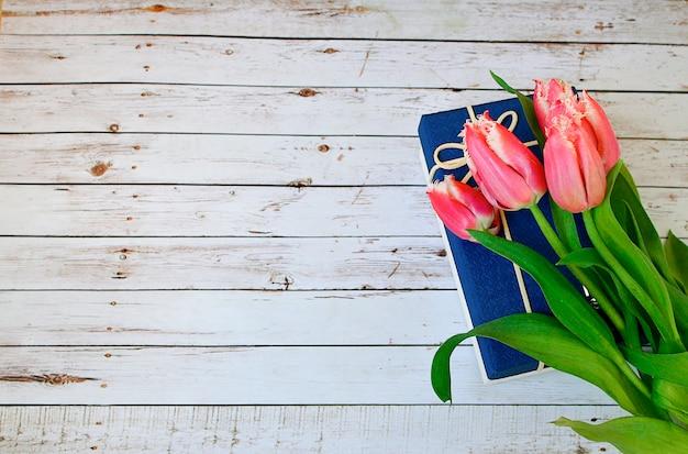 Różowe tulipany kiść i niebieski prezent na białe drewniane deski rustykalne stodoła wiejski stół tło.