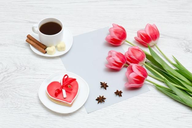 Różowe tulipany, kubek kawy i czerwone pierniczki