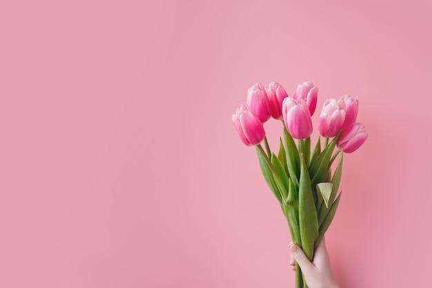 Różowe tulipany na różowym tle z miejsca na kopię.