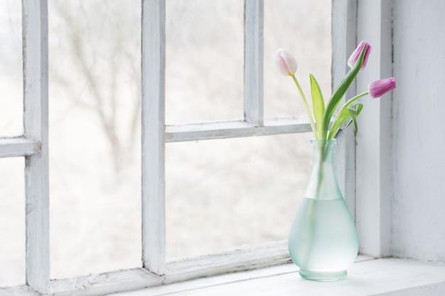 Różowe tulipany na starym białym parapecie