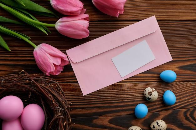 Różowe tulipany, pisanki i koperta z pozdrowieniami na drewnianym stole. wiosenne kwiaty kwitnące i paschalne jedzenie, świeża dekoracja kwiatowa, symbol święta