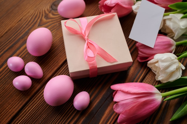 Różowe tulipany, pisanki i pudełko na drewnianym tle