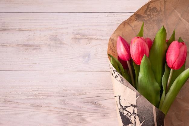 Różowe tulipany są zawinięte w papier pakowy