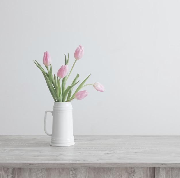 Różowe tulipany w białym ceramicznym dzbanku na drewnianym stole na tle białej ściany