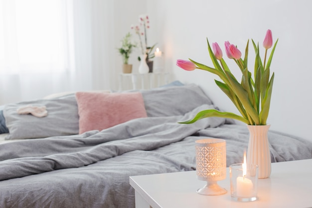 Różowe tulipany w wazonie w przytulnej sypialni