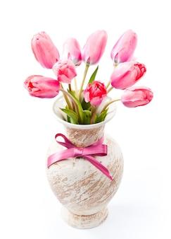 Różowe tulipany w wazonie z kokardą na białym tle