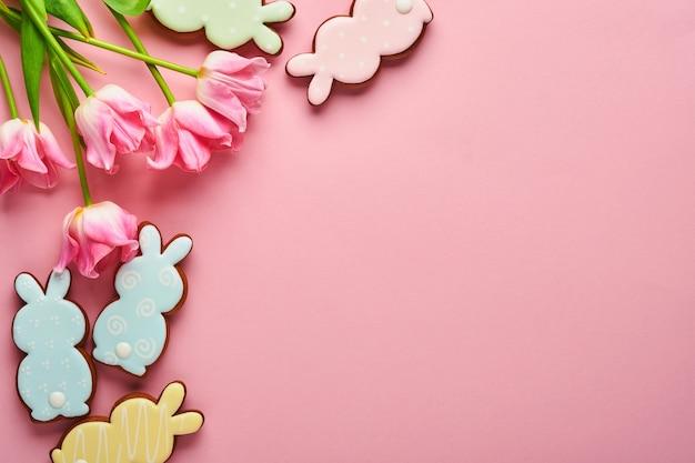 Różowe tulipany z wielkanocnymi piernikowymi jajkami umieszczonymi w rzędzie na różowym tle. kwiatowy wzór. makieta i baner. miejsce na tekst.