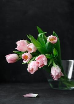 Różowe tulipany z zielonymi liśćmi w szklanym wazonie kobieta trzymająca tulipany w dłoniach kwiaciarnia kwiaciarnia bukiet na dzień matki bukiet na 8 marca bukiet dla dziewczynki na urodziny bukiet tulipanów