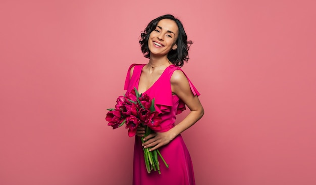 Różowe tulipany. zbliżenie wesołej damy w pięknej purpurowej sukience, która uśmiecha się, trzymając bukiet fioletowych tulipanów.