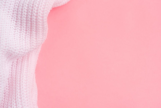 Różowe ubrania z dzianiny na różowym tle papieru