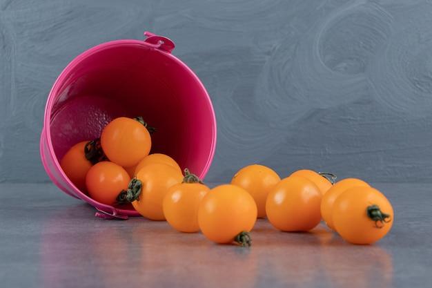 Różowe wiadro pełne dojrzałych, smacznych, żółtych pomidorów cherry
