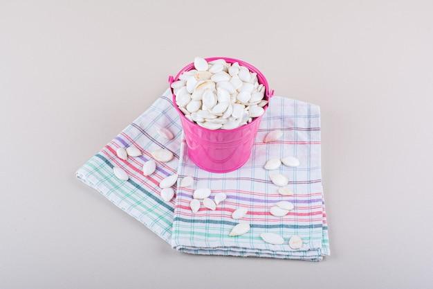 Różowe wiadro pełne organicznych nasion dyni na białym tle. zdjęcie wysokiej jakości