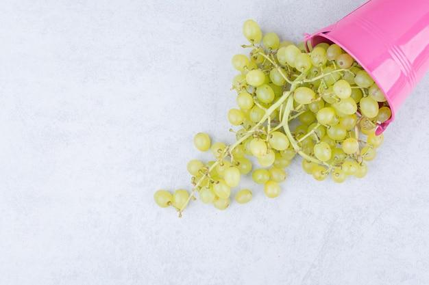Różowe wiadro pełne zielonych słodkich winogron. zdjęcie wysokiej jakości
