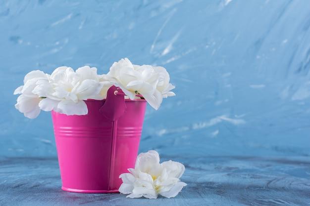 Różowe wiadro z pięknym bukietem białych kwiatów