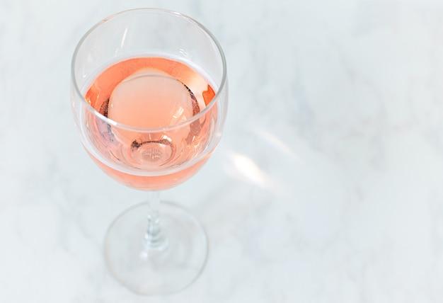 Różowe wino musujące w szklance na stole z miejsca na kopię.