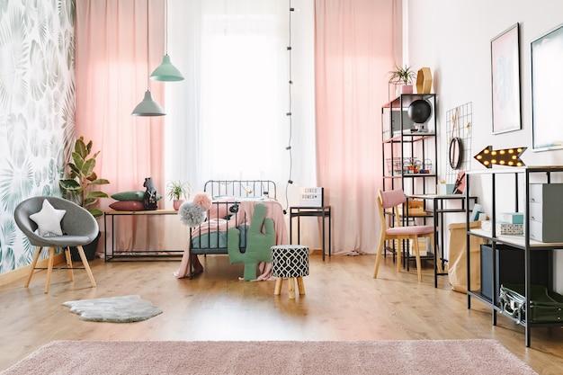 Różowe wnętrze pokoju dziewczynki z pojedynczym łóżkiem, półkami, szarym fotelem i poduszką w kształcie kaktusa