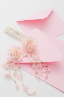 Różowe zaproszenia ślubne ozdobione są spinką do włosów panny młodej i kolczykami. przygotowanie koncepcji na wesele.