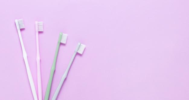 Różowe, zielone, białe i szare szczoteczki do zębów na fioletowej ścianie.