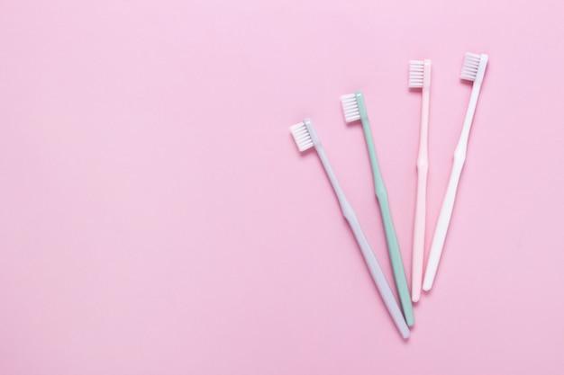 Różowe, zielone, białe i szare szczoteczki do zębów na różowej ścianie.