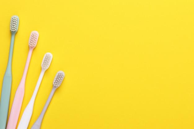 Różowe, zielone, białe i szare szczoteczki do zębów na żółtej ścianie.