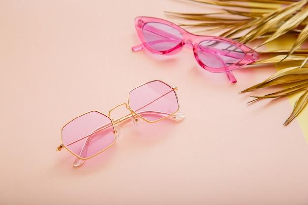 Różowe złoto kolorowe stylowe okulary przeciwsłoneczne na tle koloru letniego ze złotymi liśćmi palmowymi. modna, modna kolekcja optyki.