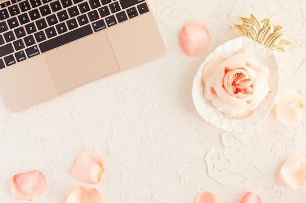 Różowego złota laptop na biurowym stole biurku z róż kwiatami i płatkami na białym z betonową teksturą