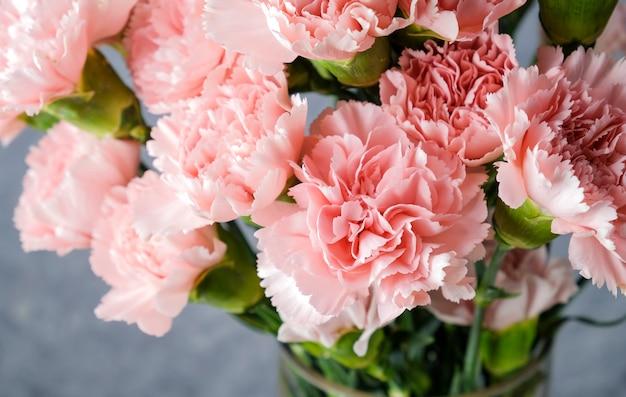 Różowi goździka kwiaty w szklanej wazie
