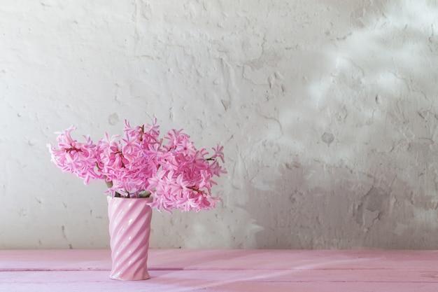 Różowi hiacynty w wazie na białym tle