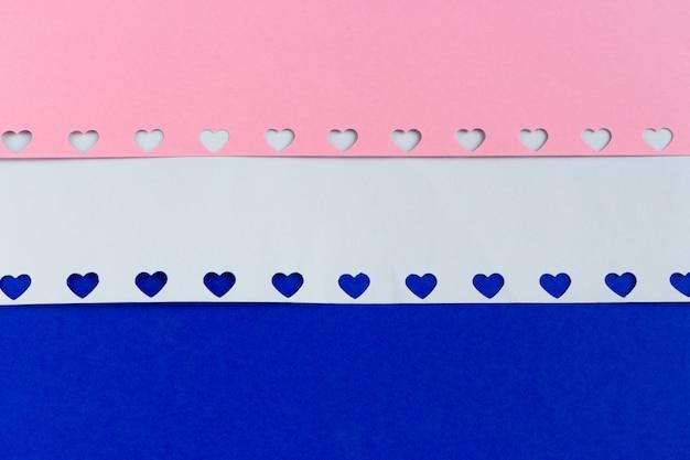 Różowi i biali papierowego serca kształtni confetti na błękitnym tle.
