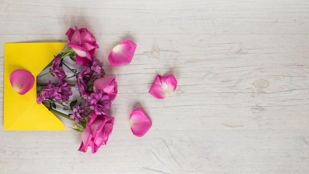 Różowi kwiaty w kopercie na stole