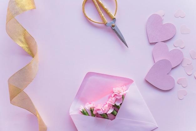 Różowi kwiaty w kopercie z papierowymi sercami na stole