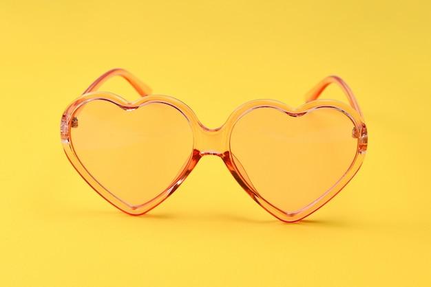 Różowi okulary przeciwsłoneczni na żółtym tle.