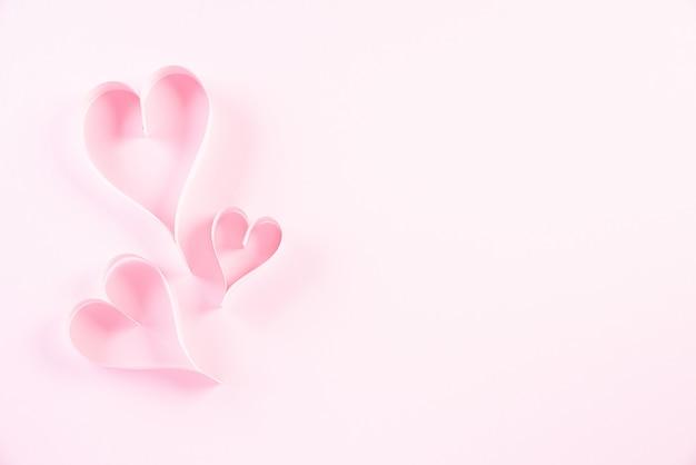 Różowi papierowi serca na menchiach tapetują tła, miłości i walentynki pojęcia ,.