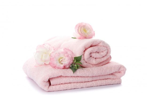 Różowi ręczniki i kwiaty odizolowywający na białym tle