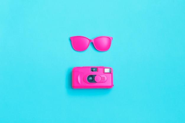 Różowi szkła i różowa kamera na błękicie