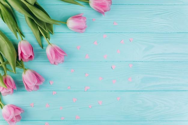 Różowi tulipany bukiet i papierowi serca na błękitnym drewnianym tle