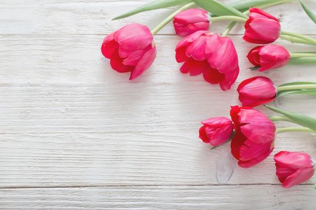 Różowi tulipany na białym drewnianym stole