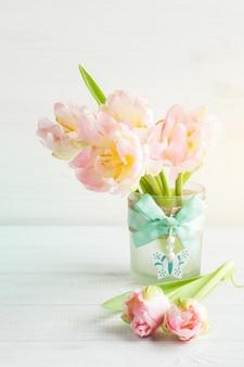 Różowi tulipany na białym drewnianym tle