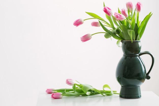 Różowi tulipany na zielonym dzbanku na białym tle