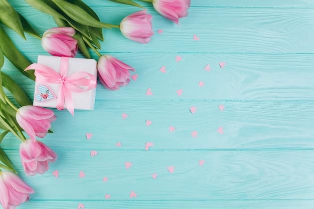 Różowi tulipany, prezent i papierowi serca na błękitnym drewnianym tle ,.