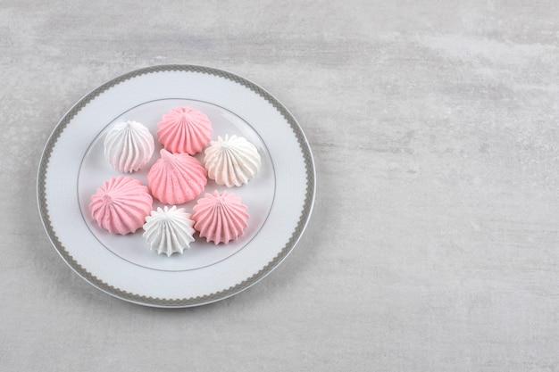 Różowo-biała beza na białym talerzu, na marmurze.