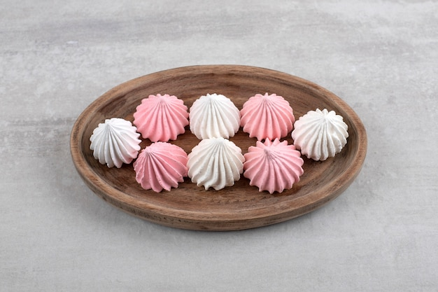 Różowo-biała beza na desce, na marmurze.