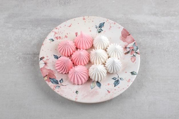 Różowo-biała beza na talerzu, na marmurowym stole.