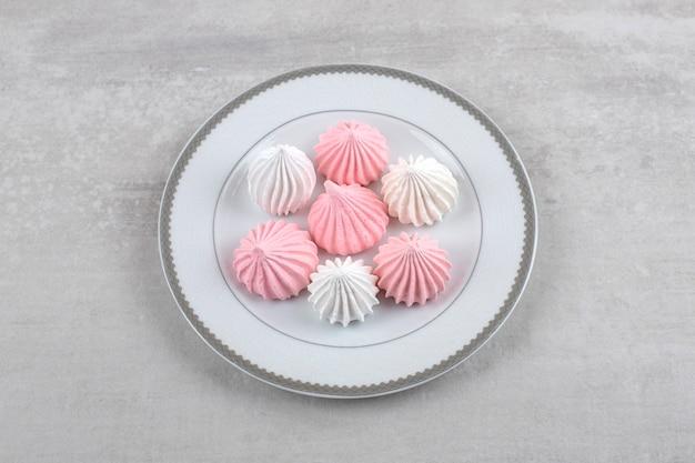 Różowo-biała beza na talerzu, na marmurze.