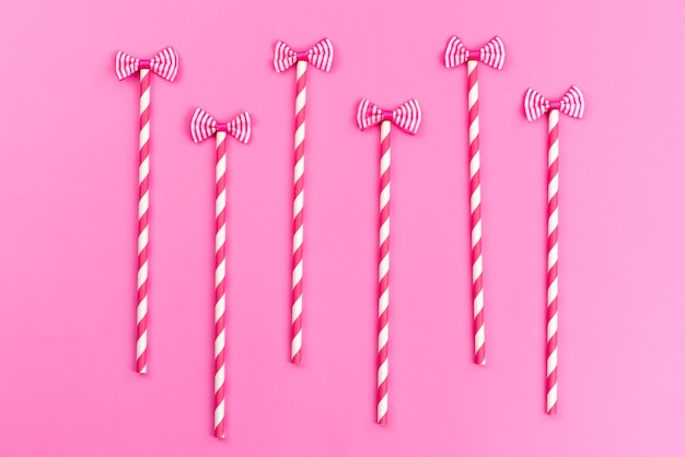 Różowo-białe cukierki w sztyfcie z widokiem z góry z uroczymi kokardkami na różowym, słodkim kolorze cukru
