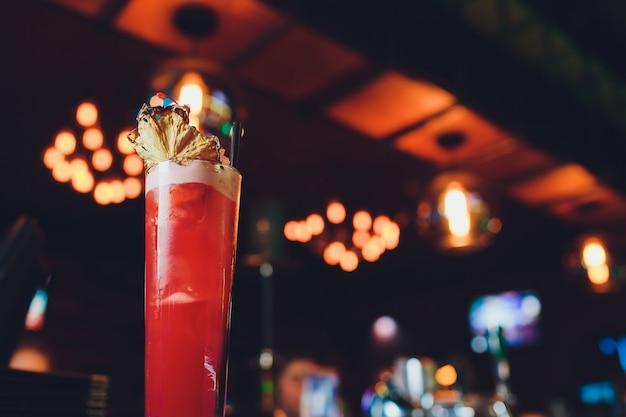 Różowo-czerwony świeży kolorowy egzotyczny koktajl alkoholowy z cytryną i lodem w barze.