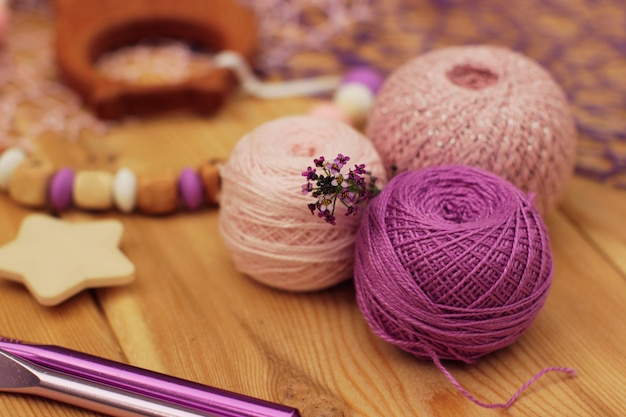 Różowo-fioletowe kuleczki i haczyki z włóczki szydełkowej.