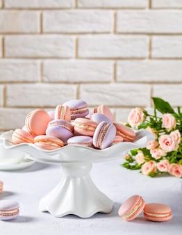 Różowo-lawendowe makaroniki na białej porcelanowej podstawce pod tort z pięknym bukietem róż na powierzchni ceglanego muru, widok pionowy